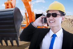 Contractor with excavator talking on cellphone Royalty Free Stock Image