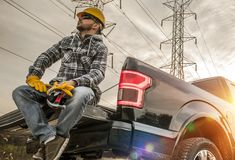 Contractor in the Field. Caucasian Field Worker with Tools. Caucasian Men Wearing Safety Gloves and Hard Hat Seating on the Back of His Pickup Truck. Contractor stock photography