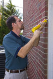 Contractor filling exterior wall cracks royalty free stock photography