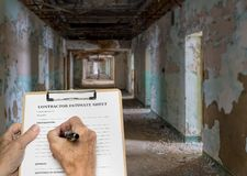 Contractor filling out estimate for abandoned office or hotel. Contractor estimate sheet for major rework of a hotel, hospital or office corridor stock photo