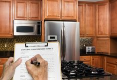 Contractor fills out estimate for modern kitchen. Contractor completing estimate form for work in a modern luxury kitchen stock image