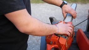 Contractor fixing a chainsaw chain on his tool ALT. 