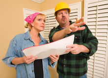 Contractor in Hard Hat Discussing Plans with Woman. Male Contractor in Hard Hat Discussing Plans with Woman in Room Royalty Free Stock Photography