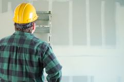 Contractor in Hard Hat Looking at Fresh Drywall. Stock Photo