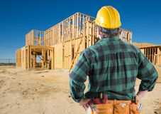Contractor with Hard Hat At New House Framing at Construction Site Stock Photo