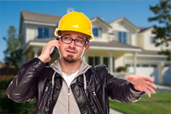 Contractor in Hard Hat on Phone In Front of House Stock Photo