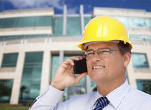 Contractor in Hardhat Talks on Phone In Front of Building Stock Photography