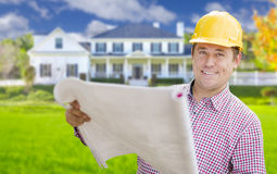 Contractor Holding Blueprints In Front of  Beautiful Custom Home Stock Image