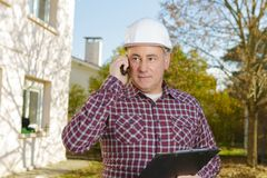 Contractor holding cost information and calling Stock Photography