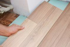 Contractor install wooden laminate flooring with insulation and soundproofing sheets. In problem area Royalty Free Stock Image