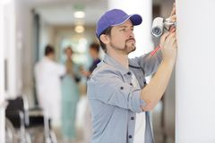 Contractor installing cctv camera in hospital royalty free stock photo