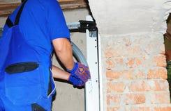 Contractor installing garage door with measuring tape. Install garage door opener springs system. Contractor installing garage door with measuring tape. Install royalty free stock image