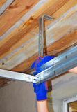 Contractor Installing Garage Door Metal Profil  Post Rail and Spring Installation and Garage Ceiling. Spring Tension Lifts Section Garage Door Panel that Royalty Free Stock Photography
