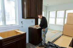 Contractor installing a laminate counter top during a kitchen remodel. Insrall counter top kitchen stock image