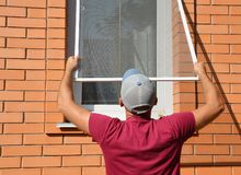 Free Contractor Installing Mosquito Wire Screen On House Window To Protect From Insects. Mosquito Wire Screen Installation Stock Photo - 138019230