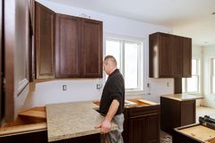 Contractor installing a new laminate kitchen counter top. Kitchen more functional with a sink, cooktop stock photos