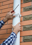 Contractor installing and repair pvc rain gutter system pipeline. Guttering, Plastic Guttering, & Drainage by Handyman hands. Contractor installing and Royalty Free Stock Image