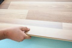 Contractor installing wooden laminate flooring with insulation and soundproofing sheets. Man laying laminate flooring. Stock Photography