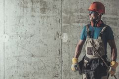 Contractor Job Concept. Caucasian Construction Worker in His 30s on the Raw Concrete Wall Background Royalty Free Stock Photo