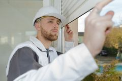 Contractor looking at window roller shutter. Window royalty free stock photos