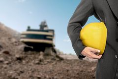 Contractor man holding a yellow helmet. On construction site Stock Photos