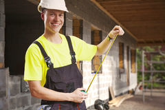 Contractor measuring at construction site Royalty Free Stock Photo