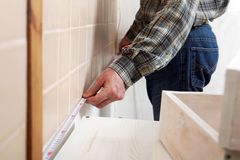 Contractor measuring a kitchen Royalty Free Stock Image