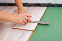 Contractor measuring a laminate piece Royalty Free Stock Image