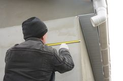 Contractor measuring wall before installing roof gutter downspout pipe. Contractor measuring wall before installing rain gutter downspout pipe stock photography
