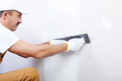 Contractor plasterer. Mature contractor  plasterer working indoors Royalty Free Stock Photography