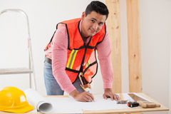 Contractor remodeling a house. Handsome young contractor working on a remodeling design for a house Stock Photography