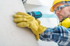 Contractor Remodeling Job. Caucasian Worker with Cordless Driller Installing Drywall Elements. Hard Hat Construction Zone royalty free stock photography