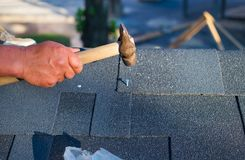 Contractor repair corner bitumen roof shingles with hammer and nails royalty free stock photos