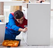 Contractor repairman assembling furniture under woman supervisio stock images