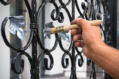 Contractor`s hand with brush that painting metal fence. Royalty Free Stock Photo