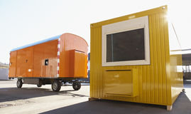 Contractor's shed. New yellow contractor's shed and orange wagon at industrial yard stock image