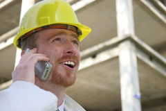 Contractor on site. Man with helmet talking on a cell phone in front of a building construction Stock Photography