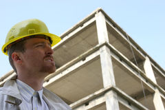 Contractor on site. Man with helmet in front of a building construction Stock Images