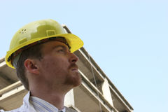 Contractor on site. Man with helmet in front of a building construction Stock Photos