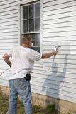 Contractor spray painting. Painter spray painting house, repairs of house is on going, house will be up for sale Royalty Free Stock Photo