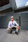 Contractor squatting at a construction site Stock Photo