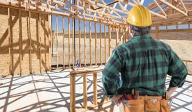 Contractor Standing Inside Construction Framing of New House. Stock Photos