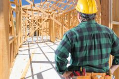 Contractor Standing Inside Construction Framing of New House. Contractor Standing Inside Construction Framing of a New House stock photo