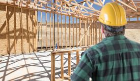Contractor Standing Inside Construction Framing of New House.  stock photo
