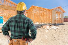 Contractor Standing Outside Construction Framing of New House. Male Contractor or Construction Worker Standing Outside Construction Framing of New House royalty free stock photos