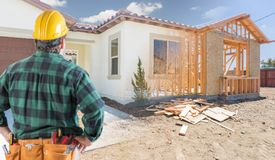 Contractor Stands at Construction Framing and Photo New House. Contractor Standing Outside Construction Framing and Photo of New House stock photography