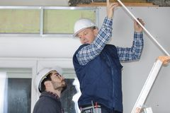 Contractor on stepladder talking to colleague on ground. Contractor on stepladder talking to colleague on the ground Stock Image