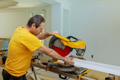 Contractor Using Circular Saw Cutting Crown Moulding for Renovation. Royalty Free Stock Photography