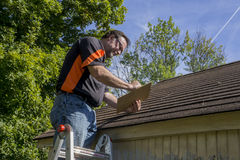 Contractor Using Clipboard To Figure Hail Damage Repair Costs. Contractor using a clipboard to figure our repiar cost for hail damaged roof Royalty Free Stock Photos