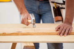 Contractor using a hammer. Closeup of a male contractor using a hammer on some nails and wood Royalty Free Stock Photo